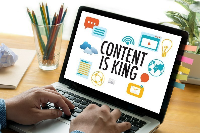 Person's hands on a laptop displaying content is king to represent content as part of a B2B inbound marketing growth plan