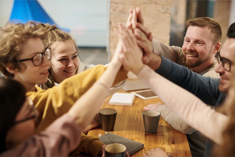 Team high fiving following the success of their B2B inbound marketing Growth Plan